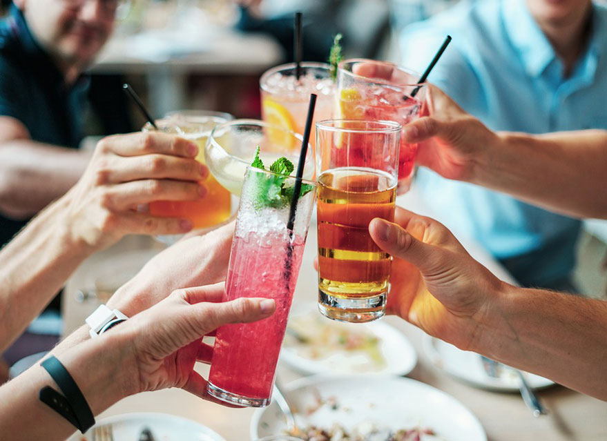 Our guide on buying a round of drinks shows a group of people doing 'cheers' with a class of drink in their hand.