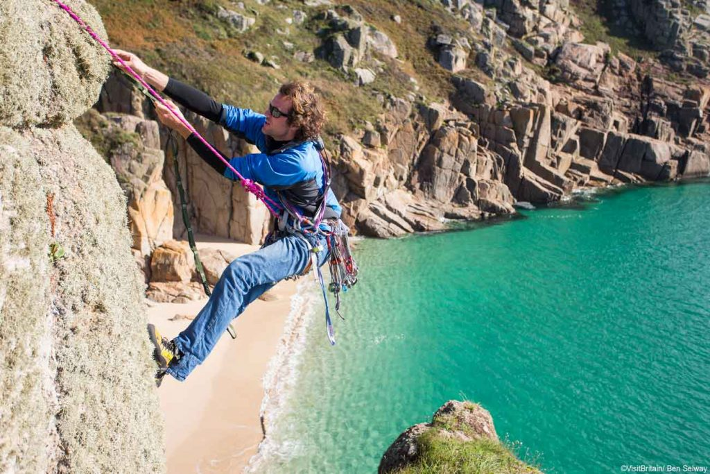 A man doing some rock climbing around Porthcurno, Cornwall, one of the best beaches in the UK.